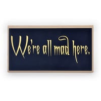 We're all mad here quote from the Cheshire cat in Alice in Wonderland metallic gold on black on a sign or plaque. S1040