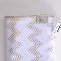 Baby blanket. Zig zag chevron print. Soft stretchy knit material. Size- 31 by 40 inches. Colors- beige and white with orange edging.